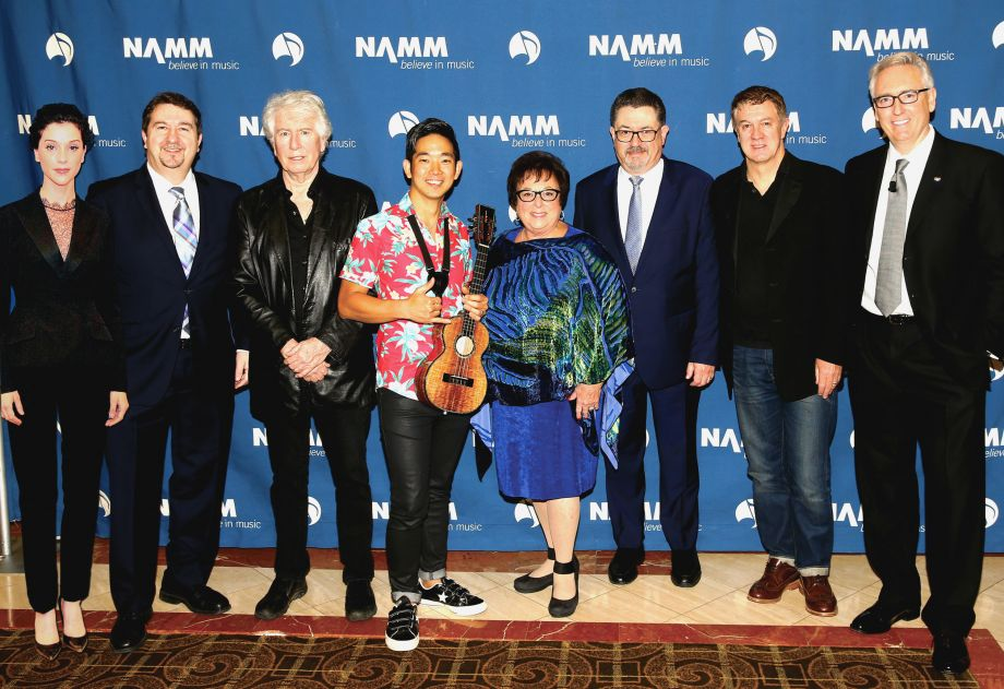 Hal Leonard President Larry Morton, Singer-songwriter Graham Nash, Composer Jake Shimabukuro, Full Compass Systems Chairman Susan Lipp, Full Compass Systems Founder and CEO Jonathan Lipp, Fender CEO Andy Mooney, NAMM President and CEO Joe Lamond along with Musician Annie Clark a.k.a St. Vincent pose backstage at the Breakfast of Champions.