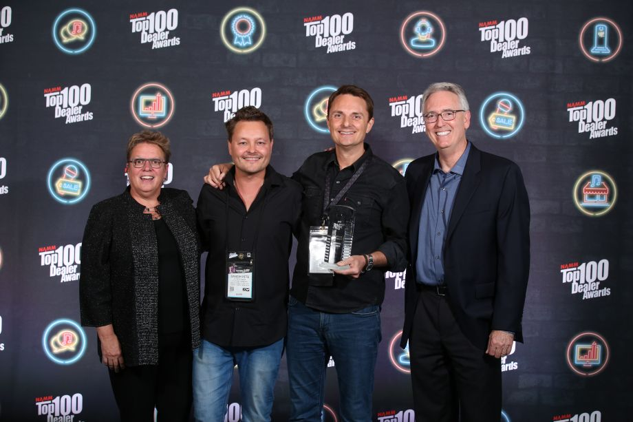 Robin Walenta (left) and Joe Lamond (right) congratulate Peter Monroe and Lee Anderton of Andertons Music Co. on their Top 100 Online Engagement Award