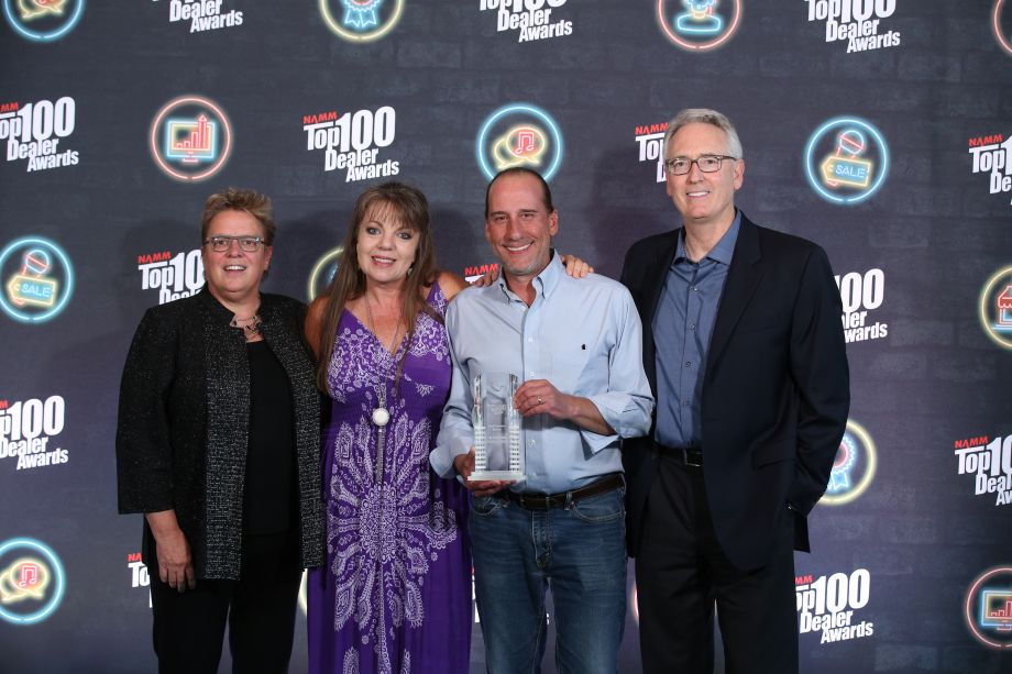 Robin Walenta (left) and Joe Lamond (right) congratulate Cindy and Rand Cook from The Candyman Strings & Things on their Top 100 Best Customer Service award.