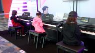 Music students practice their skills at a keyboard exhibit. (Photo by Jesse Grant/Getty Images for NAMM)