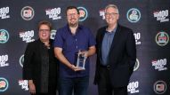 Robin Walenta (left) and Joe Lamond (right) congratulate Mark Hebert of Cosmo Music on Top 100 Best Marketing and Sales Promotion Award