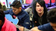 Musician Justin Emord shows a student a few chords